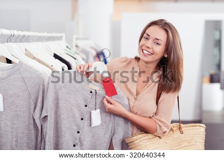 Close up Stylish Female Shopper in a Store Showing the Red Tag of a Gray Shirt at the Camera with Happy Facial Expression. - stock photo