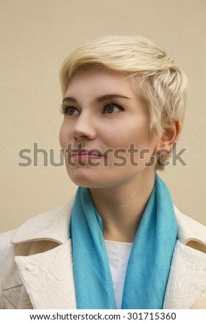 Close-up stylish portrait of beautiful young woman blonde in blue scarf, white coat on beige background. Short hair. Haircut. Hairstyle. Fringe. Professional fashion fresh nude make-up. Model shot. - stock photo
