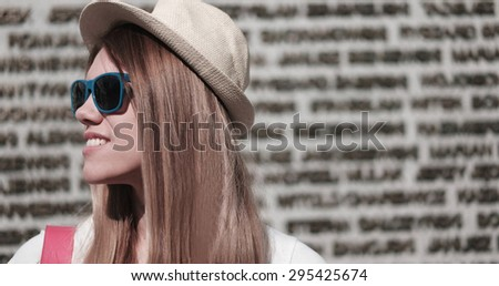 Close up Stylish Young Pretty Woman Wearing Hat and Sunglasses, Looking to the Left of the Frame Against Concrete Building Wall. - stock photo