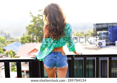 Close up summer fashion image of stunning sexy woman with perfect butt, posing on balcony, wearing luxury stylish silk blouse and grunge micro denim shorts, vacation glamour style. - stock photo