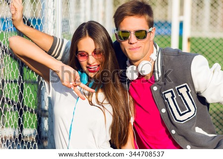 Close up  summer lifestyle portrait  of  young  fashionable couple with emotional faces , showing sings, laughing. Wearing stylish summer  sportive outfit.