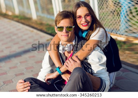 Close up summer portrait of pretty young hipster couple in love posing outdoor, urban city background, casual outfit, students smiling . Stylish  sunglasses. red lips. Cheerful woman and man.