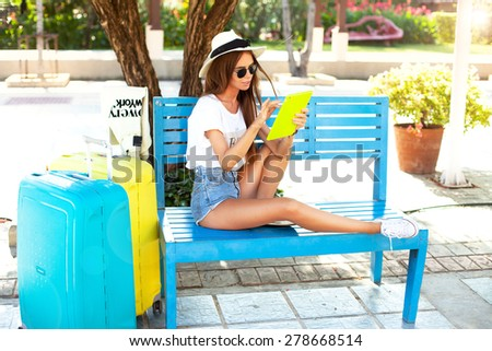 close up summer portrait of women using tablet at outdoor for relax time in park near airport,beautiful woman waiting for flight departure sitting on suitcase and use tablet,street background  - stock photo