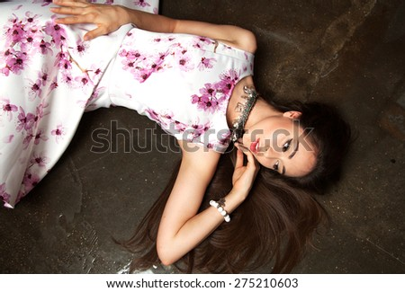 Close up summer portrait of young beautiful woman with bright make lying on floor outdoor in sunny day, wearing stylish jewelry  and accessories.Summer flower bright dress.Summer outfit.Party woman