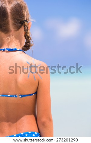 Close up sun painted by sun cream on kid shoulder - stock photo
