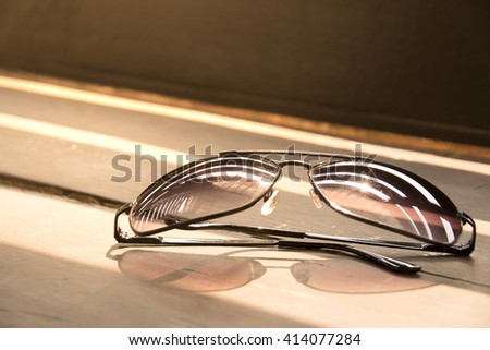 Close up sunglasses on wood floor and sunlight
