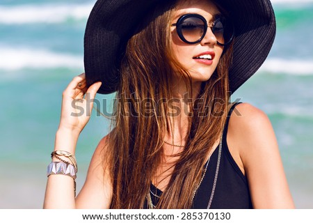 Close up sunny summer portrait of beautiful woman with fluffy brunette long hairs, smiling, having fun near blue ocean, wearing vintage sunglasses ,outfit and hat, vacation style , bright colors. - stock photo