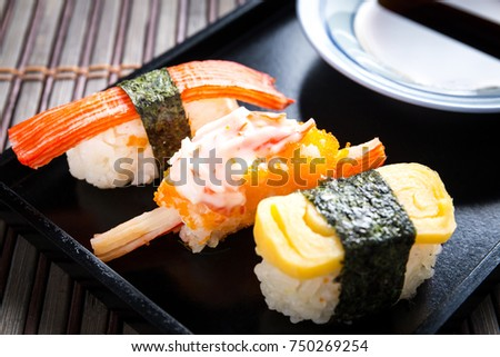 Close up Sushi set with chopsticks and soy on black plate and bamboo background.