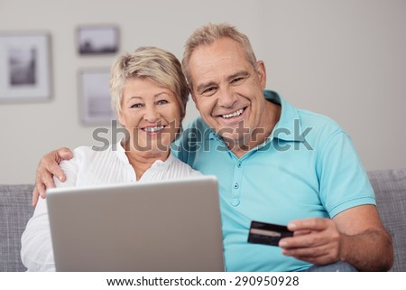 Close up Sweet Matured Couple with Laptop and Credit Card, Sitting at the Couch with Happy Facial Expression.