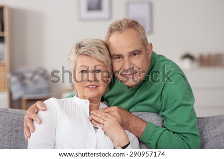 Close up Sweet Middle Aged Husband and Wife Relaxing at the Living Room, Looking at the Camera - stock photo