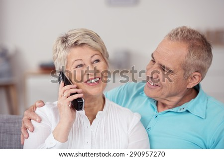 Close up Sweet Middle Aged Husband Looking at his Pretty Wife Talking to Someone on the Phone. - stock photo