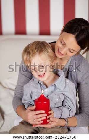 Close up Sweet Mom and Son Sitting on the Couch and Holding Lighted Big Red Candle with Smiles on their Faces. - stock photo