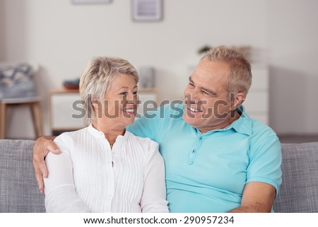 Close up Sweet Senior Husband and Wife Talking Happy Moments at the Couch In the Living Room, with Smiling Faces. - stock photo
