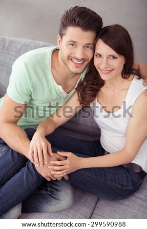 Close up Sweet Young Couple Sitting on Couch in the Living Room, Smiling at the Camera from High Angle View. - stock photo