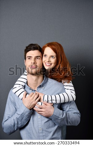 Close up Sweet Young Lovers Looking Afar While Pretty Girlfriend Hugging her Good Looking Man, Captured in Studio on a Gray Wall Background. - stock photo