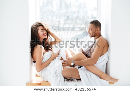 Close-up sweet young lovers smiling at the camera while sitting near the glass window indoors - stock photo