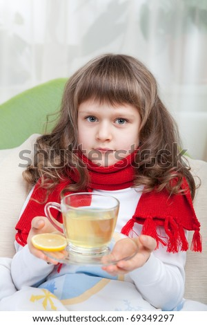 Close-up sympathetic little sick girl wrapped in red scarf under blanket in bed is drinking antiviral with lemon slice from transparent cup - stock photo