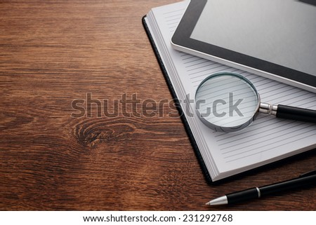 Close up Tablet Gadget and Magnifying Glass on Top of Open Notes, Resting on Wooden Table at the Right Edge, with Copy Space on Left Side for Texts. - stock photo