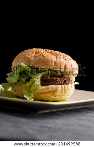 Close up Tasty Burger with Vegetarian Rissoles and Fresh Lettuce on White Plate, Dine on a Table. Isolated on Black Background. - stock photo
