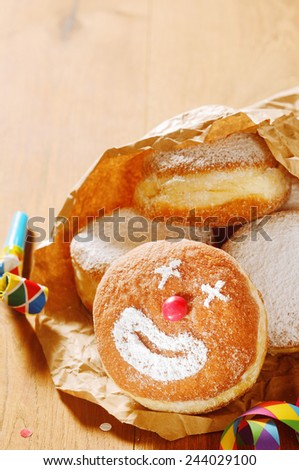 Close up Tasty Donuts on Paper with Clown Face Design on Top of Wooden Table. - stock photo
