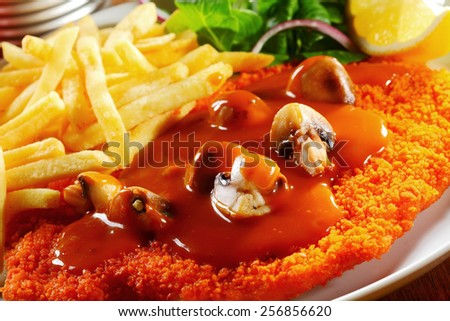 Close up Tasty Gravy on Crispy Escalope with Mushrooms Paired with Potato Fries - stock photo