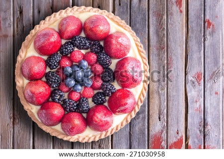Close up Tasty Homemade Tart with Fresh Berry Fruits on Top of a Rustic Table, Captured in High Angle View. - stock photo