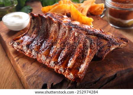 Close up Tasty Juicy Grilled Pork Rib on Wooden Cutting Board with Fried Potatoes and White Cream Sauce. - stock photo