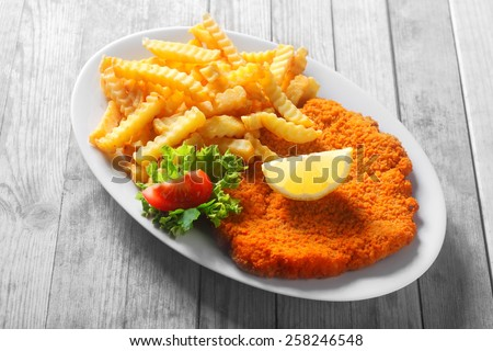 Close up Tasty Recipe of Crumbled Escalope with Potato Fries, Styled with Slice of Lemon and Tomato and Lettuce. - stock photo