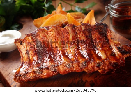 Close up Tasty Roasted Juicy Pork Rib on Wooden Chopping Board - stock photo