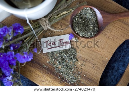 close up tea time tag with dried tea on wooden board - stock photo