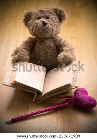 Close up Teddy bear hold blank mulberry book sit on wooden floor wait for someone to write something with pink pen ,photo in grunge vintage style - stock photo