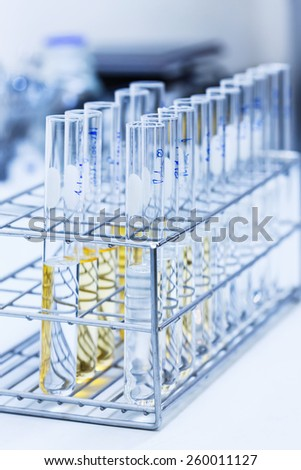 Close up test tube with white and yellow solution in rack