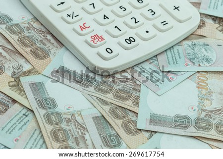 Close up Thai money in one thousand type banknotes with calculator - stock photo