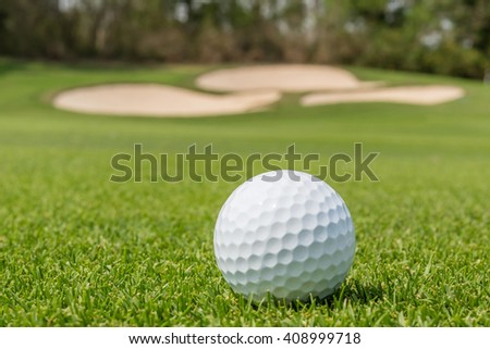 Close up the Golf ball on grass with blurred green golf course background. - stock photo