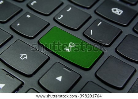Close-up the Hourglass, Sand Glass, Sand Clock symbol on the keyboard button and have Green color button isolate black keyboard