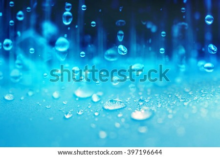 Close up the rain water drops falling on blue sponge surface as abstract background - stock photo