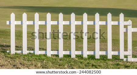 Close up the white wooden fence with green meadow background.