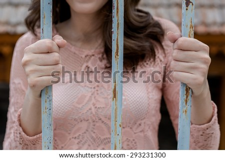 Close up thin focus on young woman hand in pink dress hole on rust iron bark in dark tone color - stock photo