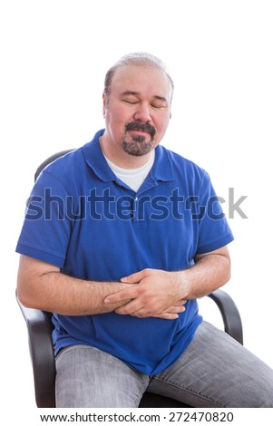 Close up Thoughtful Adult Man in Blue Polo Shirt, Sitting on a Chair with Eyes Closed and Holding his Stomach, Emphasizing Acceptance. Isolated on White Background.