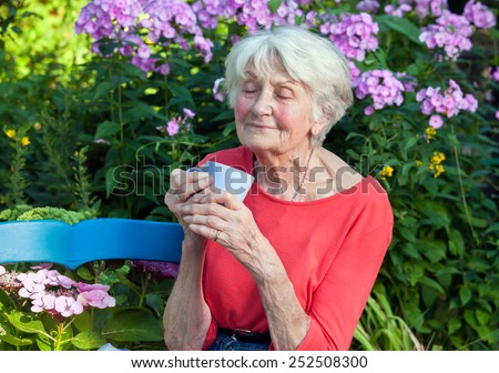Close up Thoughtful Old Woman Enjoying the Aroma of her Coffee at the Garden. - stock photo