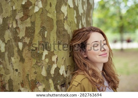 Close up Thoughtful Pretty Blond Teen Girl Leaning her Back Against Huge Tree Trunk with Eyes Closed and Smiling Face. - stock photo