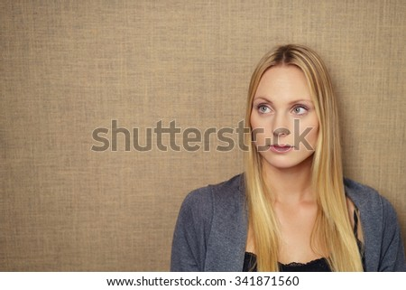 Close up Thoughtful Young Woman Looking Up Against Brown Wall with Copy Space on the Left Side. - stock photo