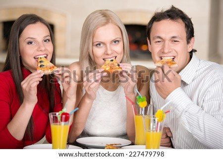 Close-up  three friends  are eating tasty pizza and drinking juice. - stock photo