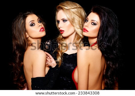 Close up Three Pretty Sexy Women with long Wavy Hair  Posing Like a Star in Elegant Dresses. Isolated on Black Background. - stock photo