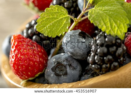 Close up tilted view on strawberries, blackberries and blueberries with little sprig of mint on top.