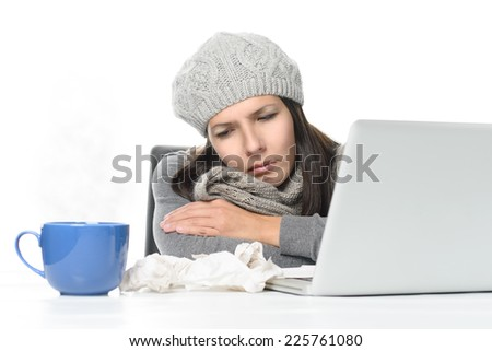 Close up Tired Sick Woman in Gray Winter Attire Working with Her Laptop While Having Cup of hot tea on Desk, isolated on White Background. - stock photo