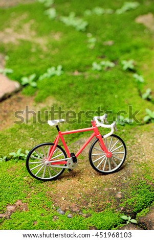 close up to a small plastic bicycle toy standing on bricks that covered with small grass and plants environment. Selective focus to a bicycle.