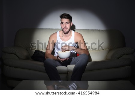 Close up to amazed young man watching movies and eating popcorn. Indoor. - stock photo