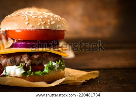 Close up to beef burger with cheese and vegetables.Blank space for text on the right side  - stock photo