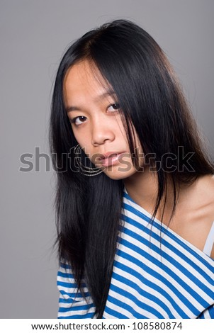 Close up to brunette in a frock.Asian girl isolated on grey background. - stock photo